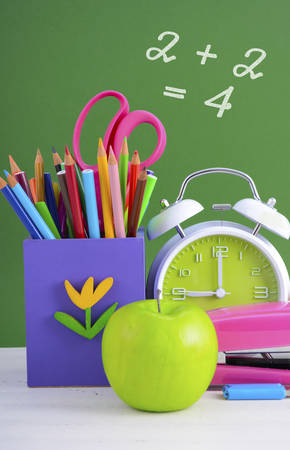 back to school supplies: Back to School or Education Concept with classroom desk and bright colored stationery supplies on white wood rustic table and green board background. Stock Photo