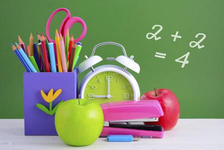 utiles escolares: Regreso a la escuela o concepto de educaci�n con el escritorio en el aula y brillantes papeler�a de colores en madera blanca mesa r�stica y el fondo verde bordo. Foto de archivo