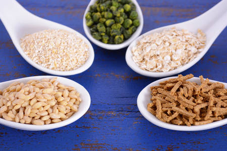 prebiotic: Healthy High Fiber Prebiotic Grains in serving spoons, including wheat bran cereal, oat flakes, dried legume peas, oat bran and pearl barley, on rustic dark blue wood table. Stock Photo
