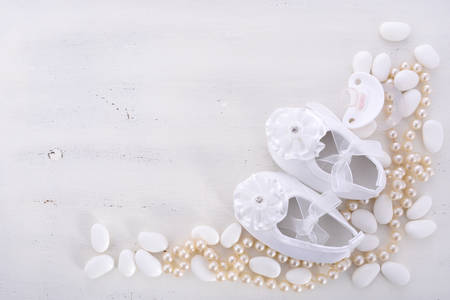 baby shoe: Baby shower neutral white background with baby booties, pearls, and sugar almonds on shabby chic rustic wood table, with copy space.