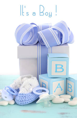 booties: Baby shower Its a Boy blue gift, with gift box, baby booties and dummy on pale blue shabby chic rustic wood table.