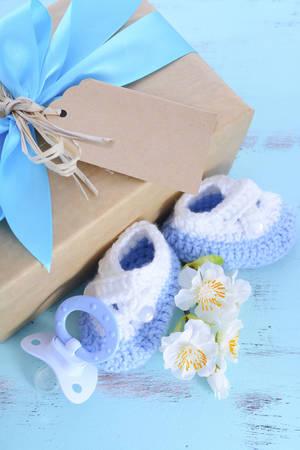 ベビー シャワーのギフト ボックス、少年自然のラップ贈り物赤ちゃんブーティと淡いブルーみすぼらしいシックな素朴な木のテーブルにダミーします。 写真素材 - 42754863
