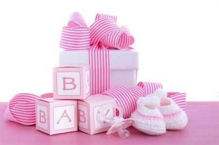 Baby shower en flicka rosa gåva med baby tossor, dummy och presentförpackning på rosa shabby chic trä bord. Stockfoto