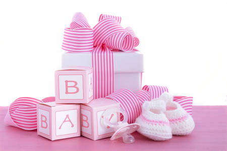 Baby shower Its a Girl pink gift with baby booties, dummy and gift box on pink shabby chic wood table.