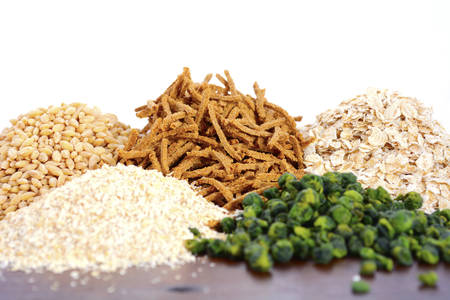 close up food: Stack of Healthy High Fiber Prebiotic Grains including wheat bran cereal, oat flakes and pearl barley, on rustic dark wood table background with white background.