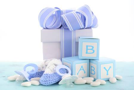 battesimo: Baby shower E 'un blu regalo Ragazzo, con confezione regalo, stivaletti bambino e manichino su azzurro pallido shabby chic rustico tavolo di legno.