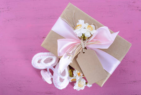 its a girl: Baby shower Its a Girl natural wrap gift with gift box, baby booties and dummy on pink shabby chic rustic wood table.