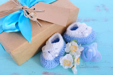 Douche van de baby zijn een jongen natuurlijk wrap geschenk met geschenkdoos, babyslofjes en pop op lichtblauwe shabby chic rustieke houten tafel.