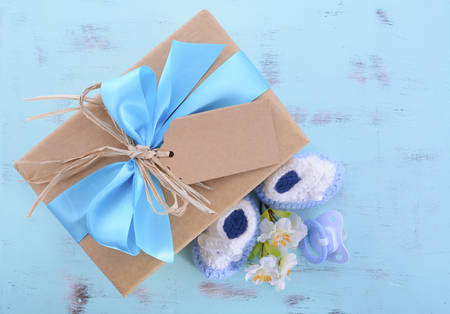 Baby shower Its a Boy natural wrap gift with gift box, baby booties and dummy on pale blue shabby chic rustic wood table.