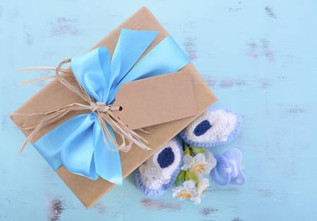 Douche van de baby zijn een jongen natuurlijk wrap geschenk met geschenkdoos, babyslofjes en pop op lichtblauwe shabby chic rustieke houten tafel. Stockfoto - 42754878