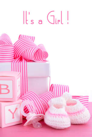 baptism: Baby shower Its a Girl pink gift with baby booties, dummy and gift box on pink shabby chic wood table.