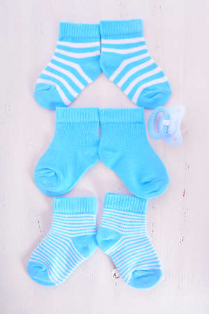 its: Its a Boy Baby Shower or Nursery concept with socks and pacifier dummy on white shabby chic  wood