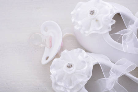 Baby shower neutral white background with baby booties, pearls, and sugar almonds on shabby chic rustic wood table, with copy space.