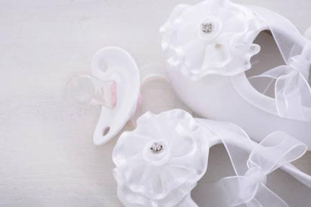 Baby shower fondo blanco neutro con zapatitos de bebé, perlas y almendras de azúcar en la mesa de madera rústica shabby chic, con copia espacio. Foto de archivo - 42790017