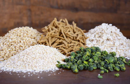 prebiotic: Stack of Healthy High Fiber Prebiotic Grains including wheat bran cereal, oat flakes and pearl barley, on rustic dark wood table background.