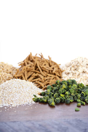 prebiotic: Stack of Healthy High Fiber Prebiotic Grains including wheat bran cereal, oat flakes and pearl barley, on rustic dark wood table background with white background.