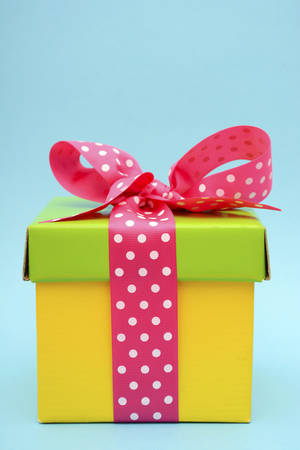 Bright color yellow and green gift box with pink polka dot ribbon on pink and blue background. Imagens - 43183854