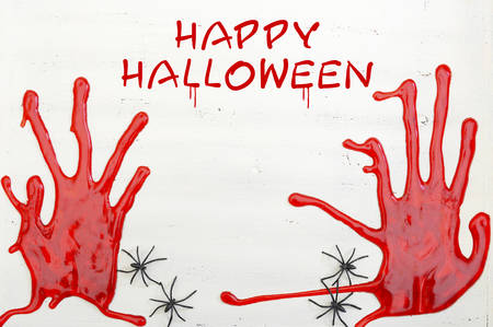 bloody hand print: Halloween rustic white wood background with bloody hand prints and spiders, with Happy Halloween text.