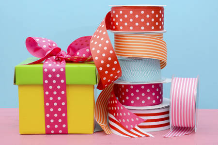 Birthday or special occasion gift wrapping with bright color gift box and rolls of colorful ribbon.