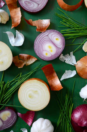 onion peel: Onions, chives and garlic scattered on old green wood table for food preparation and cooking concept.