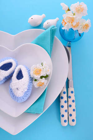 its a boy: Its a Boy blue theme baby shower table place setting with heart shape plates on blue table background. Stock Photo