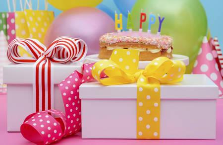 Tableau lumineux et coloré de fête avec des ballons et des cadeaux avec des rubans de couleurs vives et des arcs, et gâteau de joyeux anniversaire sur le stand de gâteau. Banque d'images - 43183981