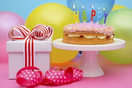 Bright colorful party table with balloons and gifts with bright color ribbons and bows, and Happy Birthday cake on cake stand.