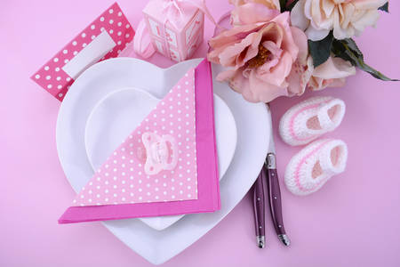 baby cutlery: Its a Girl pink theme baby shower table setting with heart shape plates on pink table background.