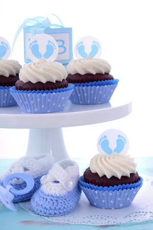 baby shower boy: Its a Boy Blue Baby Shower Cupcakes with baby feet toppers and decorations on shabby chic blue wood table.