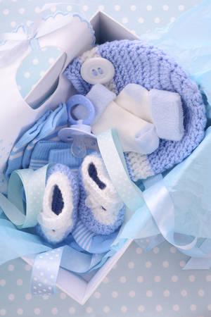 Son bleu boîte de cadeau de douche de Boy thème de bébé avec des vêtements de bébé, bavoir, bonnet, chaussons, chaussettes et tétine. Banque d'images