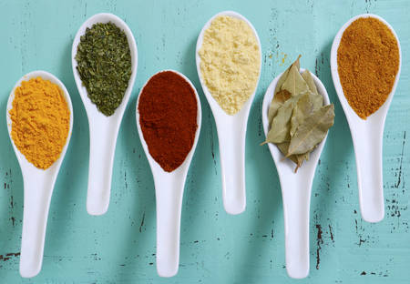 indian mustard: Colorful cooking spices and herbs in white spoons on vintage aqua blue table overhead. Stock Photo