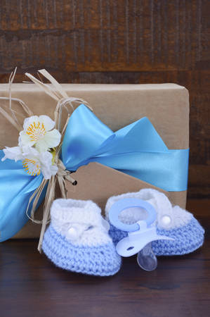 baby boy announcement: Baby Shower Gift with Booties and Pacifier on Rustic Dark Wood Background.