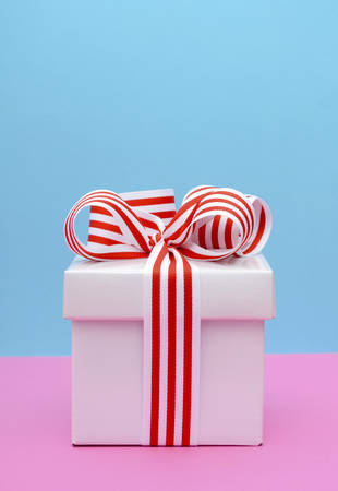Bright gift box with red and white stripe ribbon on pink and blue background. Reklamní fotografie - 43184358