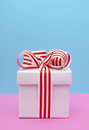 Caja de regalo brillante con cinta raya roja y blanca sobre fondo de color rosa y azul. Foto de archivo - 43184358