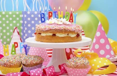Tabla colorido brillante del partido del feliz cumpleaños con globos, serpentinas, bolsas de regalo del favor de fiesta y pastel de cumpleaños con velas encendidas. Foto de archivo - 43184360