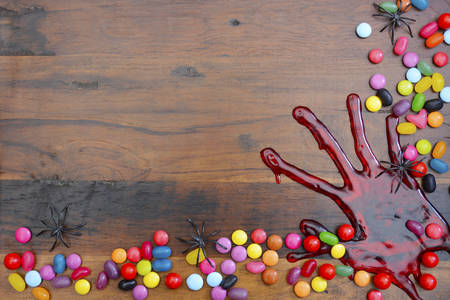 gory: Halloween rustic dark wood background with bloody hand prints and candy, with copy space for your text here.