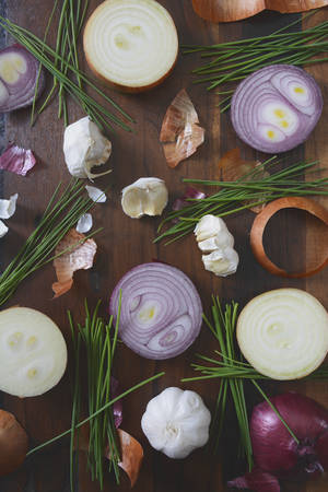 peel: Onions, chives and garlic scattered on wood table for food preparation and cooking concept, with applied retro vintage style filters.