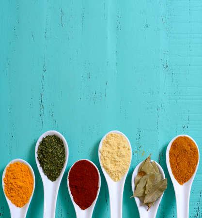 Kleurrijke koken specerijen en kruiden in witte lepels op vintage aqua blauwe lijst overhead met copyspace voor uw tekst hier.