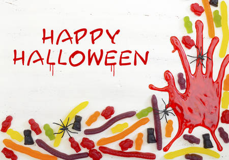 ghoulish: Halloween rustic white wood background with bloody hand prints and candy, with Happy Halloween text.