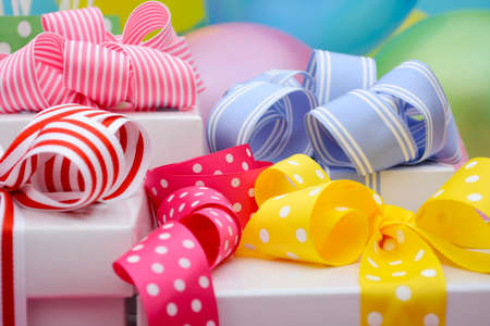 gift bags: Bright colorful party table with balloons, streamers, party favor gift bags and gifts with bright color ribbons and bows. Stock Photo