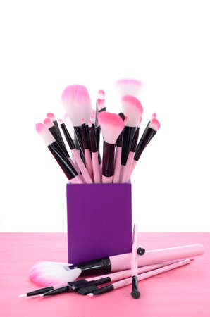 make up brush: Artists makeup pink brush set in purple container on pink wood table.