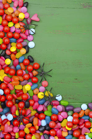 ghoulish: Halloween rustic green wood background with candy and spiders, with copy space for your text here. Stock Photo