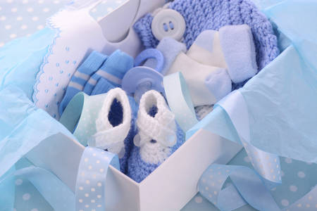 it's: Its a Boy blue theme baby shower gift box with baby clothes, bib, bonnet, booties, pacifier and socks. Stock Photo