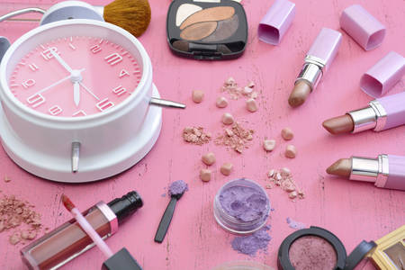 make up products: Early morning makeup routine and products on vintage shabby chic pink wood table. Stock Photo