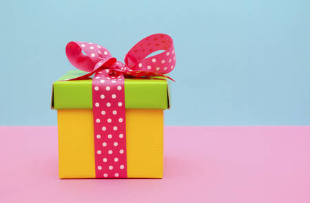 Bright color yellow and green gift box with pink polka dot ribbon on pink and blue background.