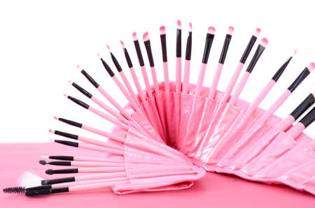 sets: Artists makeup brush set in pink leather pouch bag on pink wood table. Stock Photo