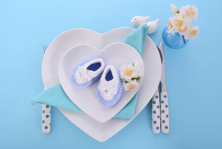 it's: Its a Boy blue theme baby shower table place setting with heart shape plates on blue table background. Stock Photo