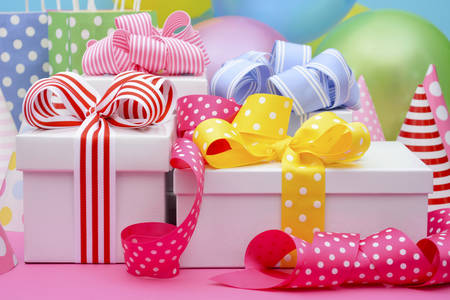 party favors: Bright colorful party table with balloons, streamers, party favor gift bags and gifts with bright color ribbons and bows. Stock Photo