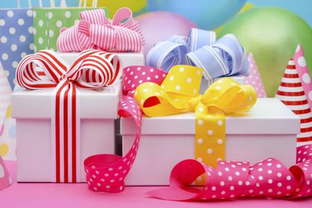 Heldere kleurrijke feesttafel met ballonnen, streamers, party gunst gave tassen en geschenken met heldere kleur linten en strikken.