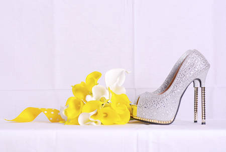 arum: Pair of silver rhinestone high heel shoes and yellow and white arum lily bouquet on white background for wedding and bridal accessory concept.